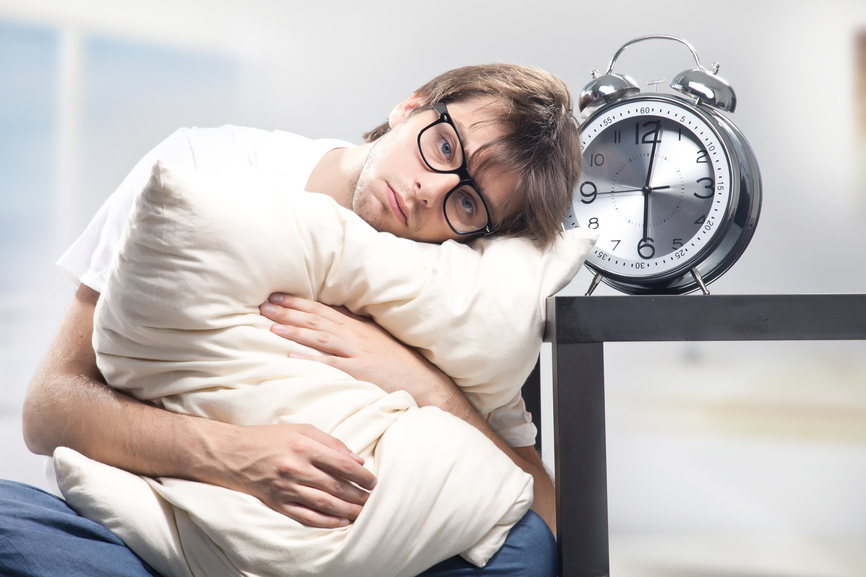 Sad man holding pillow