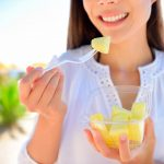 bigstock-Pineapple--woman-eating-slice-80114699