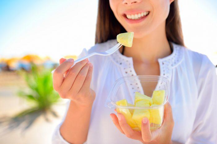 bigstock-Pineapple--woman-eating-slice-80114699