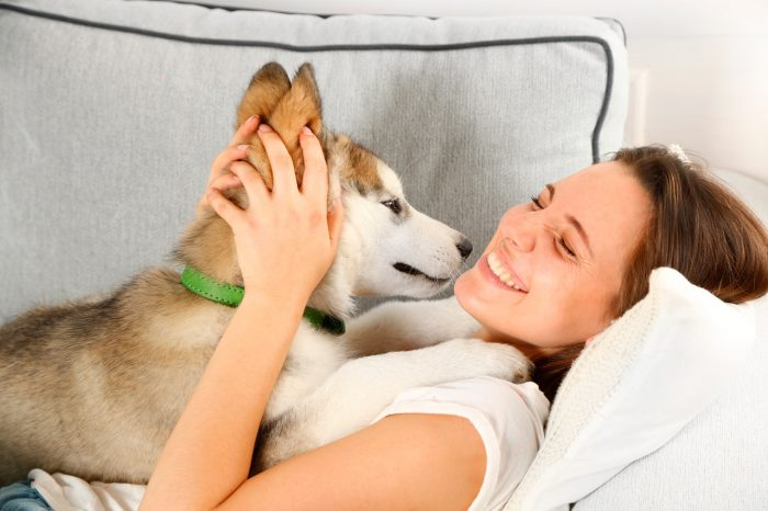 bigstock-Woman-lying-with-her-malamute--100469825