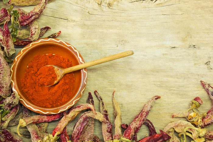 Wooden spoon of cayenne pepper in bowl with cayenne pepper on wooden table. With paste space.