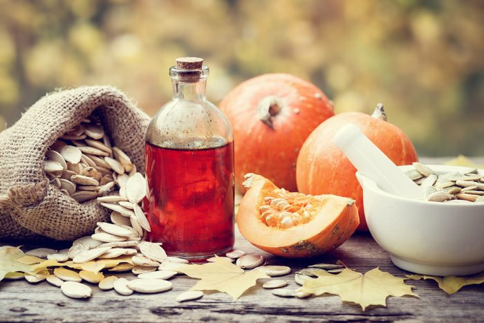 Pumpkin seeds oil bottle pumpkins canvas bag with seeds and mortar on wooden table. Selective focus.
