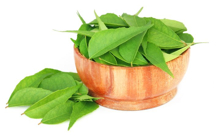 Curry Leaves in a wooden bowl over white background