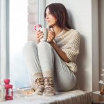 Happy Beautiful Woman Drinking Hot Coffee Sitting On Window Sill