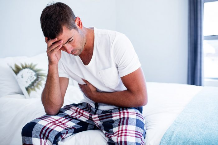 Young man sitting with stomach pain on bed in bedroom