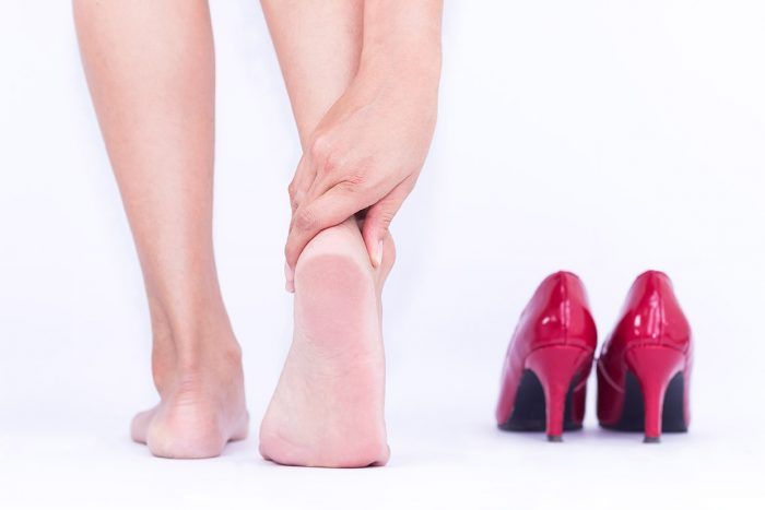 Heel pain in women Woman massaging her foot.