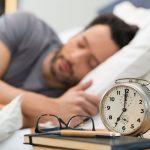 Young man sleeping in his bedroom. Man sleeping with an alarm cl