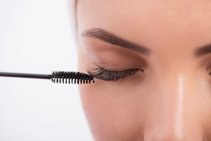 Close-up of young woman applying mascara on her long eyelash by brush